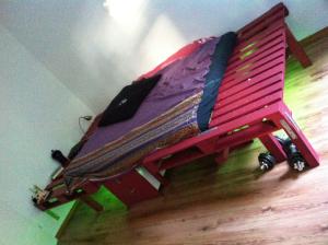 Doppelbett aus Paletten und Bauholzbalken, Schrägansicht und Neonunterbeleuchtung