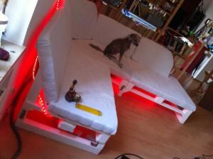 Palettensofa: Fertiges Sofa mit zufriedenem Sitzgast