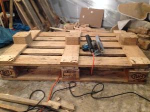 Tischplattenpalette mit Holzresten an Abstandhaltern liegt unten